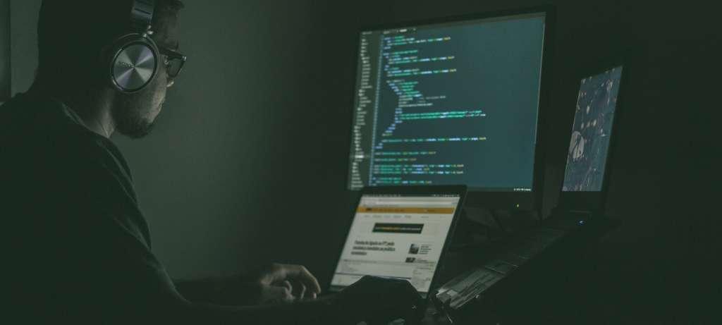 Junger Mann mit Headset im dunklen Raum vor mehreren Laptops beim programmieren. Java-Entwickler, Enterprise-Web-Anwendungen bei Syngenio.