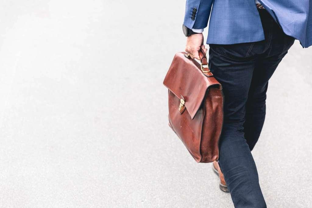 Mann im Jacket und Jeans gekleidet und Aktentasche in der Hand auf dem Weg zur Arbeit. Syngenio. Karriere Kachelbild Bankeninnovater Junior Business Consultant