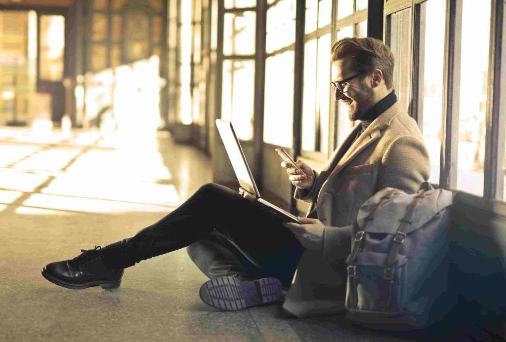 Mann im Jacket und mit Jens auf dem Boden eines langen Flores sitzend mit einem Laptop im Schoss und Handy in der Hand. Bankenversteher (Senior) Business Consultant bei Syngenio.