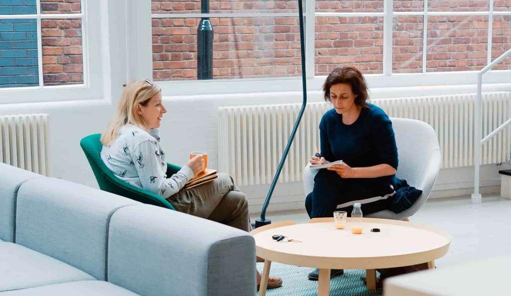 Zwei Frauen sitzen in einem sehr modernen Büro vertieft in ein Gespräch. IoT- und Cloud Consultant bei Syngenio.