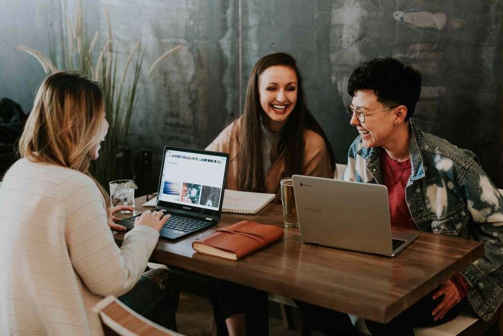 Mehrere junge Menschen lachend an einem Tisch mit Laptops vor ihnen. Praktikant IT Consulting bei Syngenio.