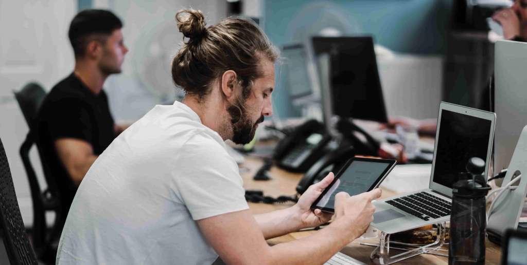 Mehrere junge Menschen sitzen mit Laptops und mobilen Geräten an ihrem Arbeitsplatz. Studentische Aushilfskraft IT-Support bei Syngenio.