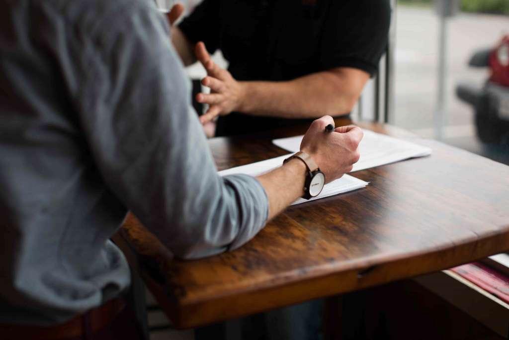 Zwei Männer besprechen an einem Tisch unternehmerische Ideen. Unternehmensgründer bei Syngenio.