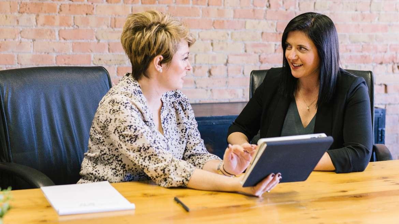 Zwei Frauen im direkten Business Austausch. Menschen und Zusammenarbeit stehen im Mittelpunkt.