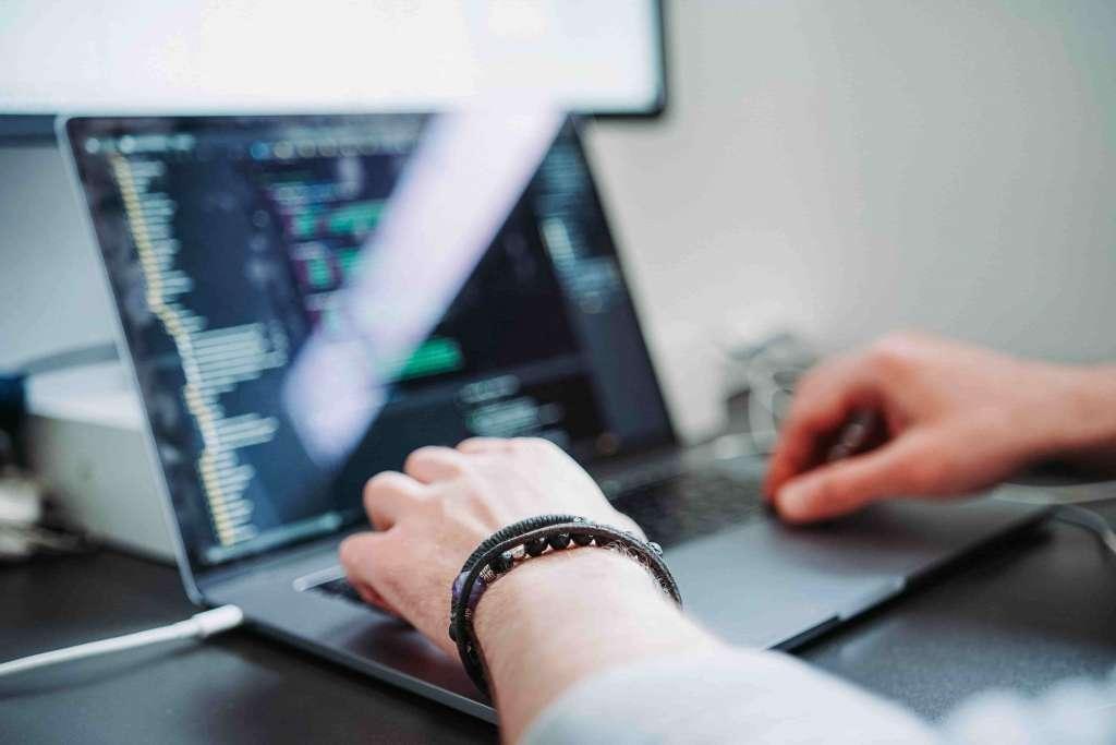 Junger Mann sitzt vor Laptop und programmiert Code. Karriere IT Consultant bei Syngenio.